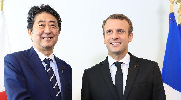 会談前に安倍晋三首相(左)と握手するマクロン仏大統領=9月20日、米ニューヨークの国連本部