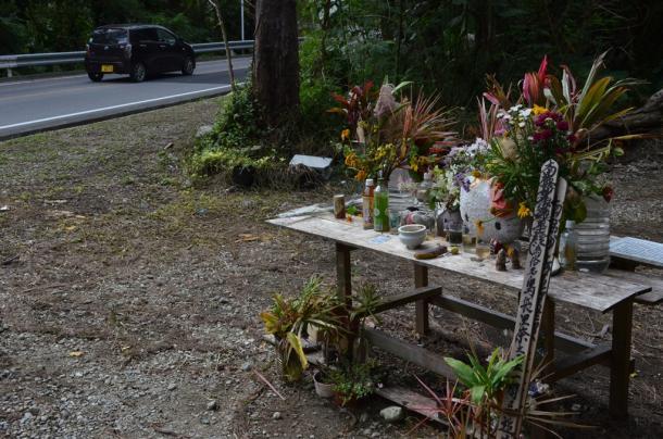 女性が遺棄された現場の献花台には、花やぬいぐるみが供えられていた=16日午前10時9分、沖縄県恩納村