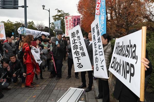 伊方原発3号機に運転差し止めの仮処分が出され、幕を掲げる弁護士ら=2017年12月13日、広島市中区