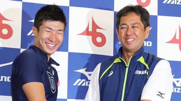9秒98の日本新記録を出した桐生祥秀選手(左)と笑顔で握手する伊東浩司・日本陸連強化委員長=2017年9月9日、福井市