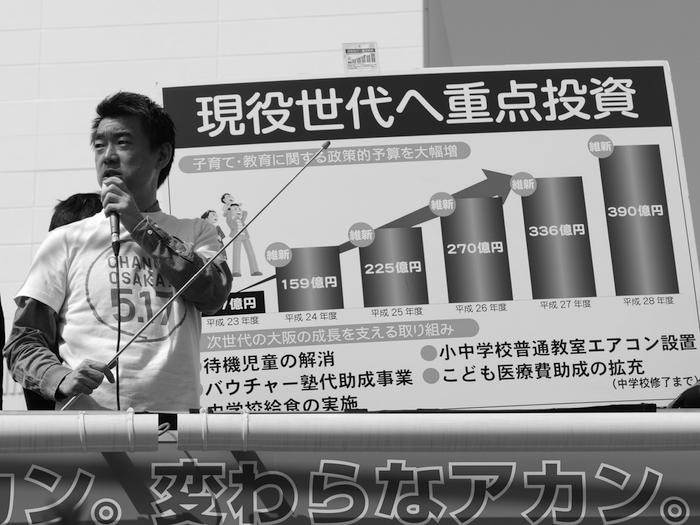 写真・図版 : 大阪維新の会の街頭タウンミーティングで、ボードを使って大阪都構想の意義を語る橋下徹代表(当時)=2015年3月30日午後、堺市西区