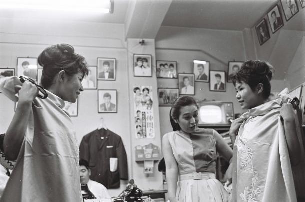 写真・図版 : 渡辺プロの事務所を訪れたザ・ピーナッツの二人に香港みやげを渡す渡辺美佐副社長=1963年