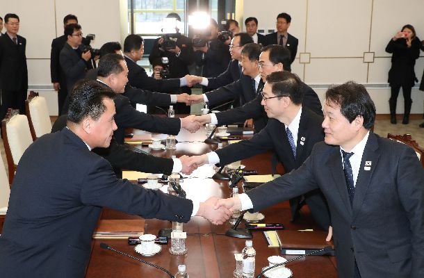 板門店の「平和の家」で握手する韓国代表団(右側)と北朝鮮代表団=2018年1月9日