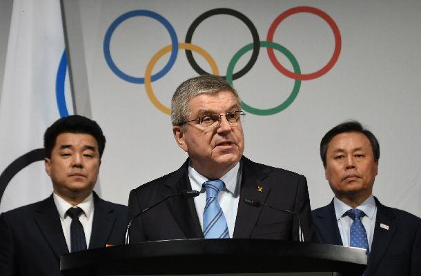 北朝鮮の金日国(キム・イル・グク)体育相兼民族五輪委員長(左)と韓国の都鍾煥(ト・ジョン・ファン)文化体育観光相立ち会いのもと、五輪初の南北合同チームを正式発表する国際オリンピック委員会のバッハ会長(中央)=2018年1月20日、スイス・ローザンヌ