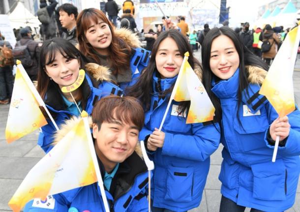 聖火リレーの旗を振って盛り上がる人たち=13日午後、韓国・ソウル