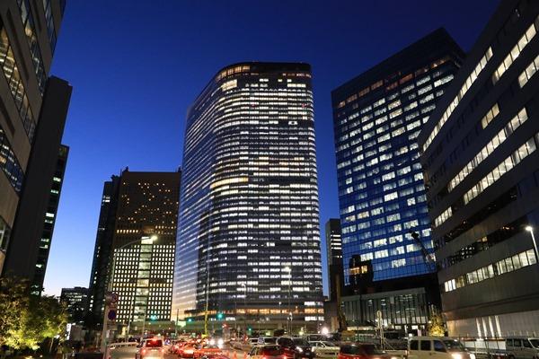 明かりがともる電通本社ビル(中央)。1987年に100%を出資し子会社として設立した電通総研を、電通は99年に吸収合併した=2016年12月28日、東京都港区東新橋1丁目