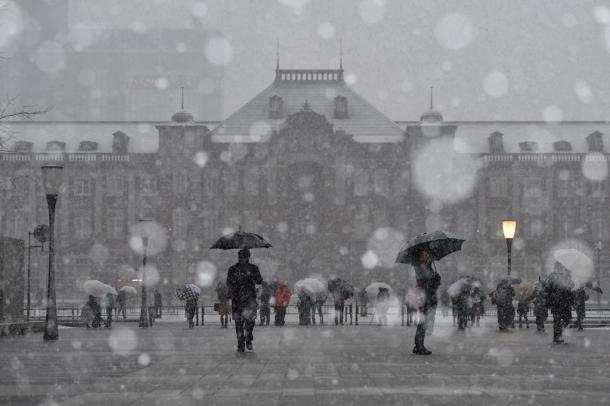 東京駅前の広場でも雪が降り続いた=22日