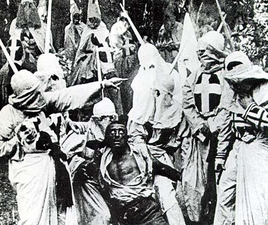写真・図版 : 【写真 6】 白人女性を襲い、KKKに捕まる黒人男性ガス  https://commons.wikimedia.org/wiki/File:Birth-of-a-nation-klan-and-black-man.jpg