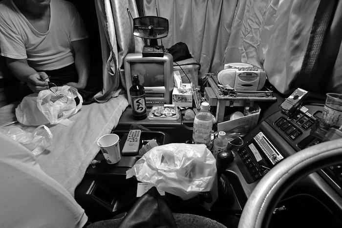 写真・図版 : 写真2 帰りの積み荷が見つからず、車内で過ごす長距離トラックの運転手(49歳)。「話し相手になれ」と車内に記者を招き入れてくれた。芋焼酎とコンビニのネギトロ巻きを楽しんでいた。(2008年4月29日午前1時32分撮影、大阪府内)