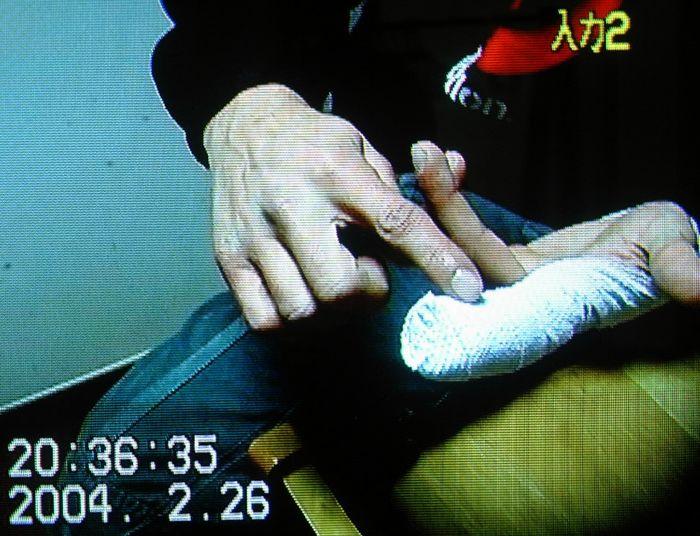 写真・図版 : 写真1 魚の加工作業中に指先を切断する労災に遭った若者。趣味のギターが弾けなくなったと涙を流した。当時、私はドキュメンタリーにも関心があり動画を回していた。(2004年2月26日午後8時36分撮影、静岡県内)