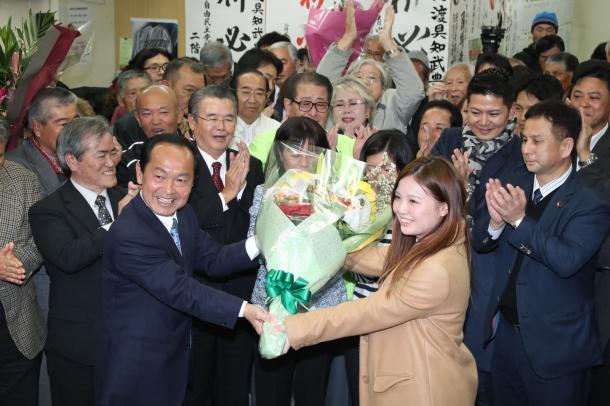 当選し長女の里沙さんから花束を受け取る前市議で新人の渡具知武豊氏=2月4日、沖縄県名護市