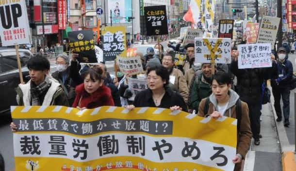写真・図版 : デモの参加者は、テンポの良い音楽のリズムに合わせて「裁量労働制はやめろ」などと声を上げた=2月、東京・JR新宿駅前