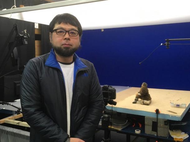 写真・図版 : 村田朋泰監督。後ろは現在制作中の『陸にあがった人魚のはなし』に登場する漁師の人形の設置された撮影台。トモヤスムラタカンパニーにて=撮影・叶精二