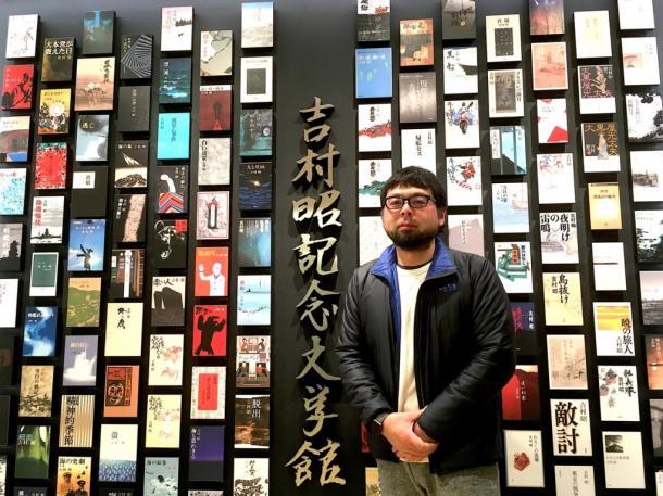 写真・図版 : 吉村昭記念文学館入口に立つ村田朋泰監督。全著作単行本表紙の展示は圧巻=撮影・叶精二