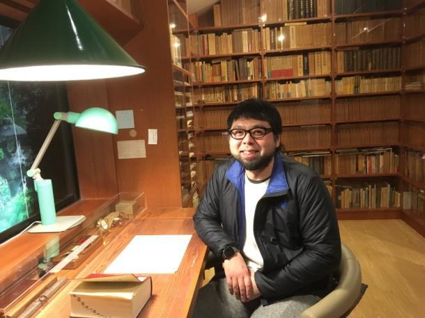 写真・図版 : 吉村昭記念文学館内の吉村氏書斎の椅子に座る村田朋泰監督。書架は郷土史書籍でギッシリ。椅子やライトも特注品=撮影・叶精二