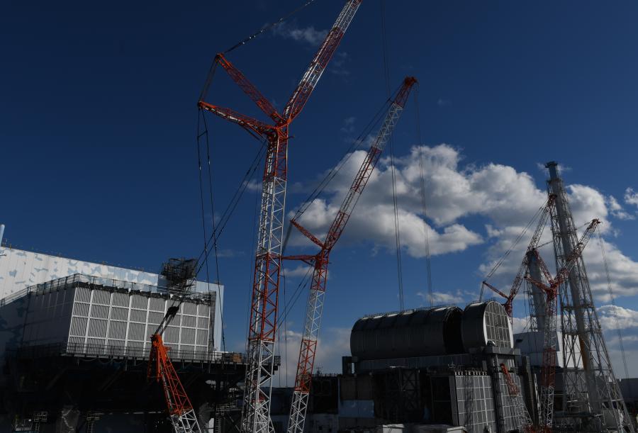 写真・図版 : 廃炉作業が進められる福島第一原発の2号機(左)と3号機=2018年2月、代表撮影