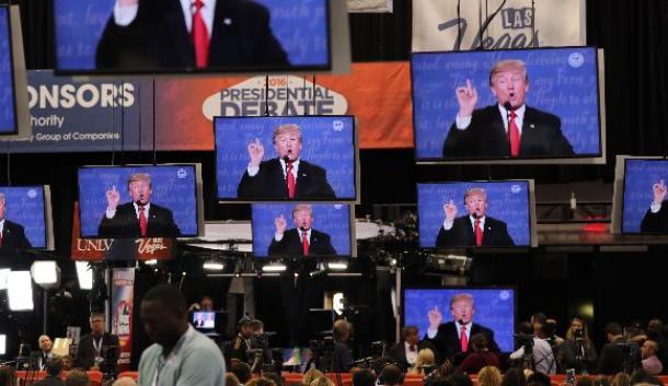 写真・図版 : テレビ討論会会場近くで討論会の中継を見る報道陣ら=2016年10月19日、米ラスベガス
