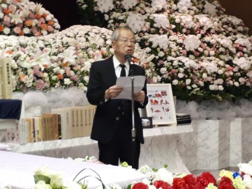 写真・図版 : 挨拶する弟の雅宣さん。板倉さんは10人兄弟の7人目だった。左側は、祭壇に対して直角に置かれた棺(ひつぎ)。こう置くことで、故人に向かって語りかけるとき参列者に顔が見えるようにした。