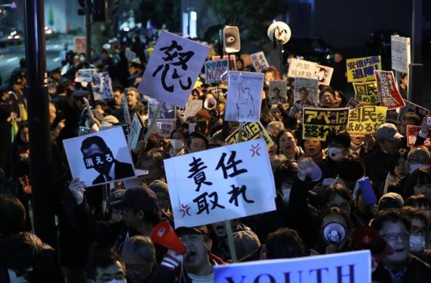 首相官邸前で、抗議のメッセージを掲げる人たち=12日午後8時42分、東京・永田町