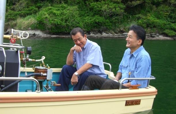 写真・図版 : 島英二さん(右)手作りの船「英光丸」に一緒に乗る加山雄三さん=2008年5月16日
