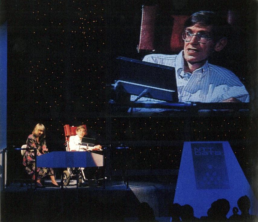 写真・図版 : 1990年9月に東京で開かれた一般向け講演会。左側でしゃべる姿が大型スクリーンに映し出された。かたわらに付き添っているのは妹のアンさん=『科学朝日』90年11月号から