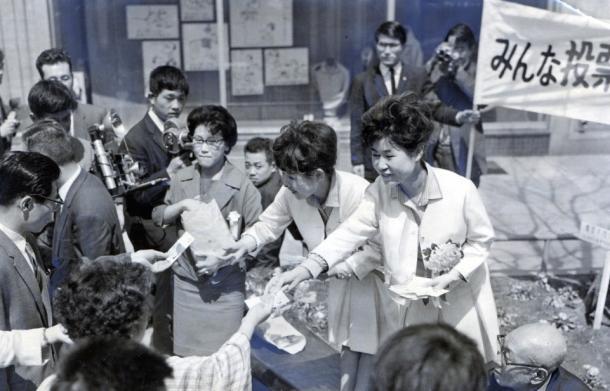 写真・図版 : 花のタネを配りながら、東京都知事、都議会議員選挙の投票を呼びかける「一日都選管委員長」のザ・ピーナッツ=1963年4月、東京・数寄屋橋公園で