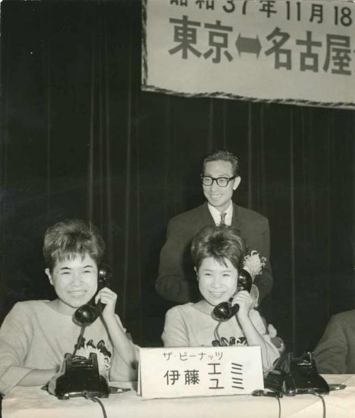 写真・図版 : 東京~名古屋の長距離ダイヤル市外通話が始まるのを記念して初通話する伊藤エミ(左)と伊藤ユミ=1962年11月、東京都千代田区