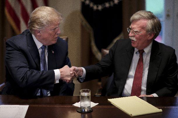 ドナルド・トランプ米大統領(左)と握手するジョン・ボルトン安全保障担当大統領補佐官=2018年4月9日(AP)