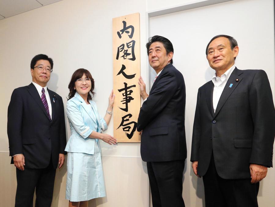 写真・図版 : 内閣人事局が発足し、看板をかける安倍晋三首相ら=2014年5月30日