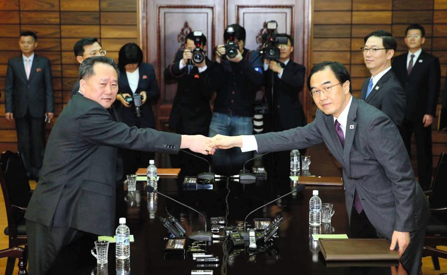 写真・図版 : 南北高官協議で握手を交わす韓国と北朝鮮の代表者=2018年3月29日、韓国統一省提供