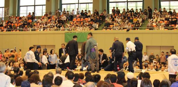 多々見良三市長が倒れた直後、土俵に駆けつけた関係者や警察官=4日午後、舞鶴市上安久の舞鶴文化公園体育館、読者提供.