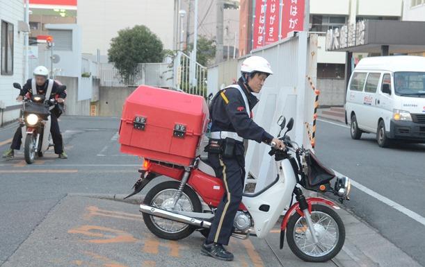 郵便物を配達する男性。日本郵政グループは正社員だけに支給してきた住居手当を廃止し非正社員との待遇格差を縮めることにした=2005年10月、群馬県太田市