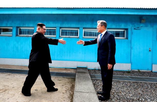軍事境界線を挟んで握手しようとして手を伸ばす金正恩朝鮮労働党委員長(左)と韓国の文在寅大統領=韓国共同写真記者団撮影.