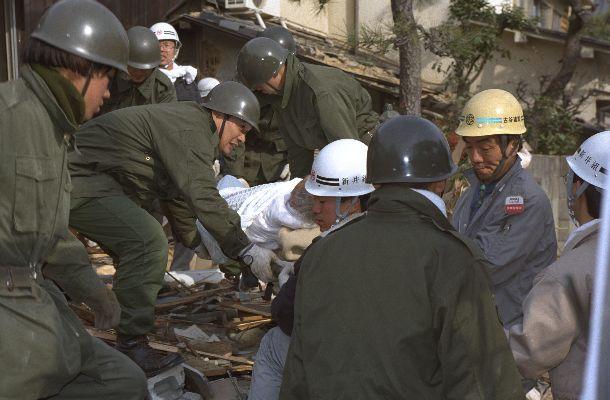 写真・図版 : 阪神大震災で崩壊した家屋から救出された被災者。自衛隊員たちが担架で運ぶ=1995年1月18日、兵庫県西宮市北口町