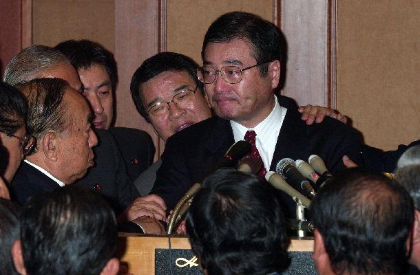 写真・図版 : 自民党の加藤紘一元幹事長による「加藤の乱」。反主流派の合同総会に出席した加藤氏は、国会に行き森喜朗内閣不信任案に賛成票を投じると発言し、議員から押しとどめられて涙を浮かべた=2000年11月20日、東京都港区のホテル