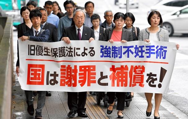 不妊手術を強制された被害者への謝罪と賠償を訴え、仙台地裁に入る原告団=2018年5月17日、仙台市青葉区