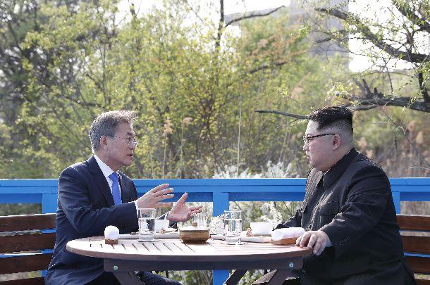 ベンチに座って話し込む韓国の文在寅大統領(左)と北朝鮮の金正恩委員長(右)=2018年4月27日、板門店