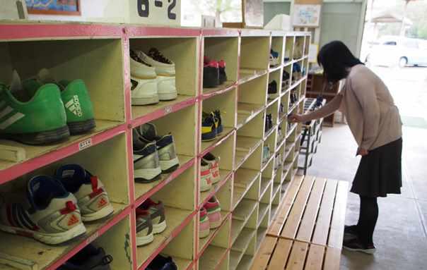 教員を支援するスクールソシャルワーカー。児童の登校後に靴箱を見回り、気になる児童の靴の破れや汚れを見る=2015年12月、福岡市