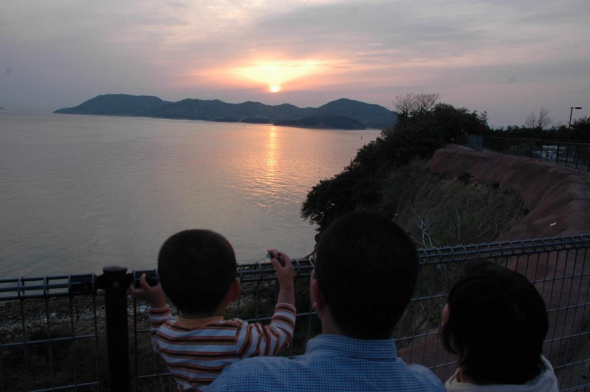 写真・図版 : 海に沈む夕日を見つめる親子(本文とは関係ありません)