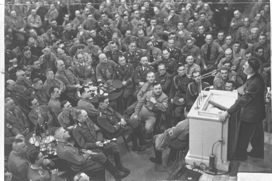 写真・図版 : ナチス幹部を前に演説するヒットラー総統。ローゼンベルグ、ゲッペルス、ヘス、ヒムラーの顔も見える=1939年11月、ドイツ・ミュンヘン