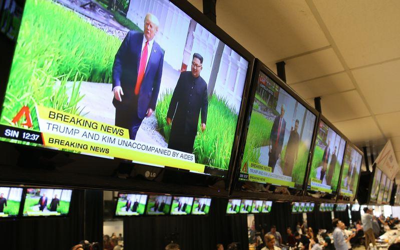 写真・図版 : ホテルの庭を散策するトランプ米大統領と北朝鮮の金正恩朝鮮労働党委員長の映像がメディアセンターに流れた=2018年6月12日、シンガポール