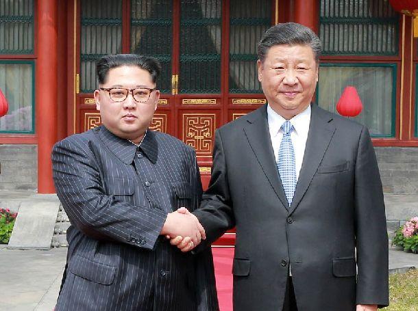 中朝首脳会談で握手する習近平国家主席(右)と金正恩朝鮮労働党委員長=朝鮮通信、2018年3月27日