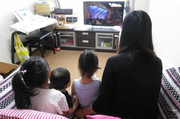 写真・図版 : 3人の子どもとテレビに見入る育児休業中の女性。「早く仕事に復帰したい」=2016年8月、東京都武蔵野市