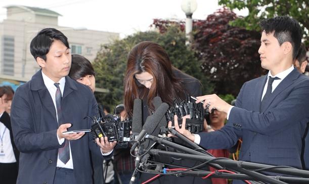 ソウル・江西警察署に出頭し、頭を下げる「水かけ姫」の趙顕旼(チョヒョンミン)大韓航空前専務(中央)=2018年5月1日、東亜日報提供