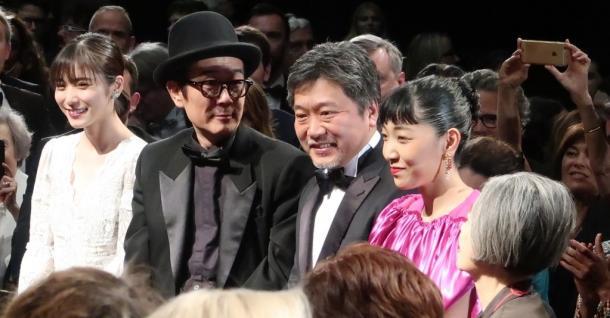 カンヌ国際映画祭で「万引き家族」公式上映が終わり、笑顔を見せる是枝裕和監督(左から3人目)と出演者のリリー・フランキーさん(同2人目)ら=2018年5月