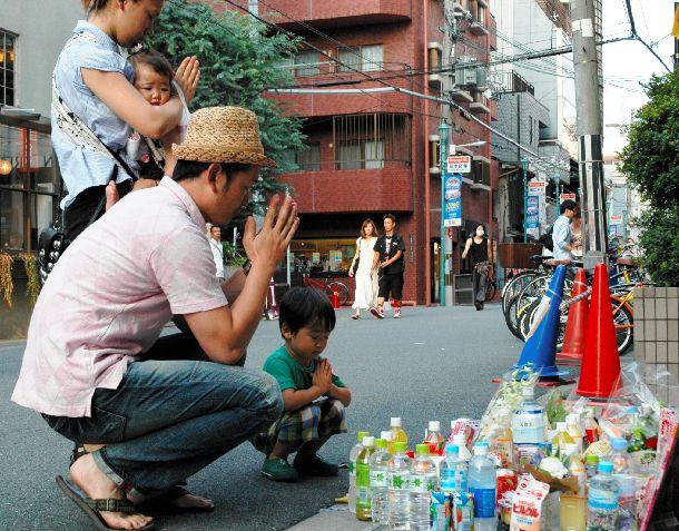大阪2児置き去り事件の現場となったマンション前で手を合わせ、亡くなった姉弟の冥福を祈る家族連れ=2010年8月1日