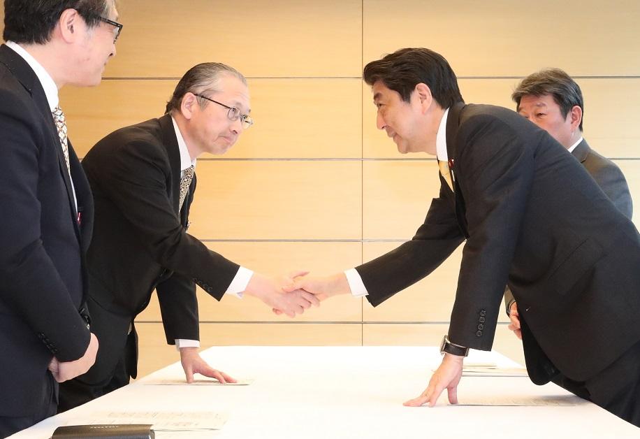写真・図版 : 安倍晋三首相と握手する神津里季生・連合会長(左から2人目)=2017年4月24日、首相官邸