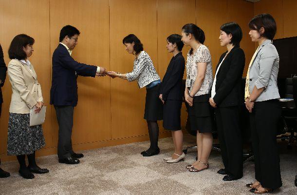 写真・図版 : 加藤勝信内閣人事局長(左から2人目)に、働き方改革についての提言書を手渡す霞が関の女性官僚たち=2014年6月26日、内閣府