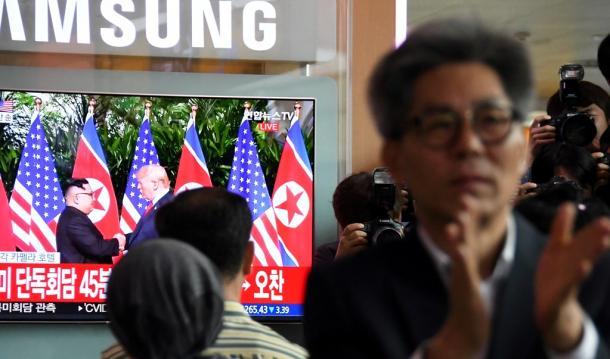 ソウル駅で米朝首脳会談を伝えるテレビを見て拍手する人20180612