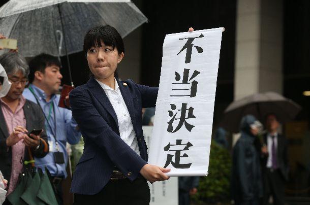 東京高裁の再審取り消し決定を受け、「不当決定」の旗を掲げる弁護士=2018年6月11日